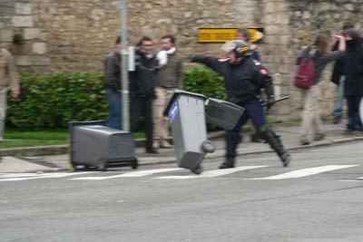 Un CRS déplace les poubelles qui sont placées sur la route pour bloquer le passge des voitures.